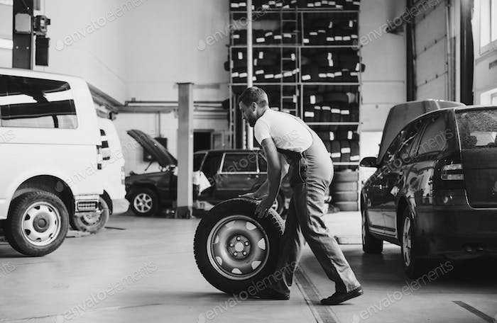 Black and white colored. Employee in uniform works in the automobile salon