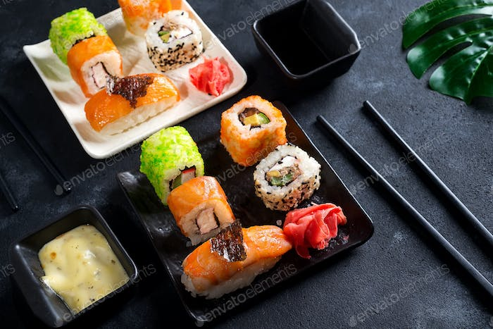 Traditional Japanese food- sushi, rolls, chopsticks, soy sauce on black slate background. Sushi menu