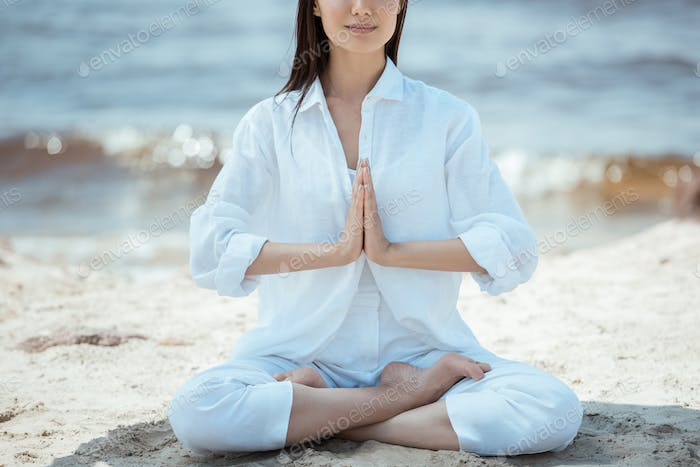 cropped image of woman in anjali mudra (salutation seal) pose on beach by sea