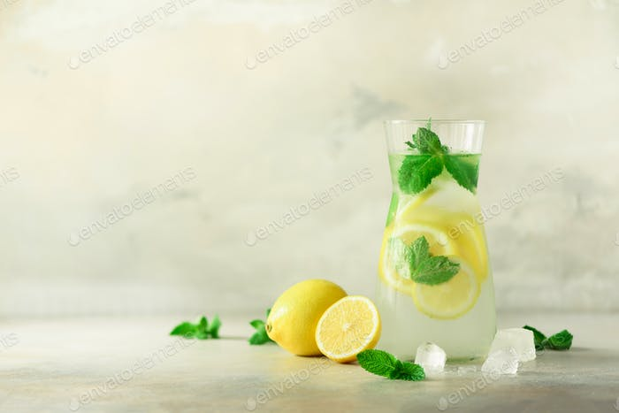 Detox water with mint, lemon on grey background. Banner with copy space, sunlight bokeh. Citrus