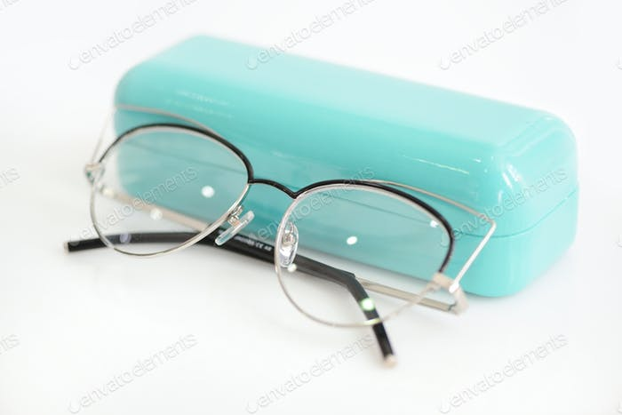Modern fashionable glasses with case on white background.