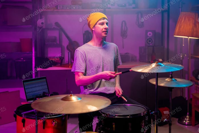 Contemporary musician in casualwear beating cymbals and drums with drumsticks