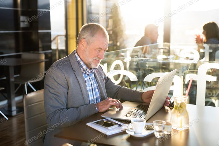 Senior businessman with smartphone and laptop in cafe