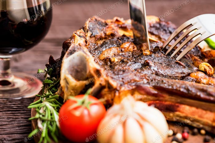 Eating beesteak with herbs and glass of wine