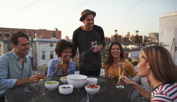 Six adult friends laughing at a table on a rooftop, close up