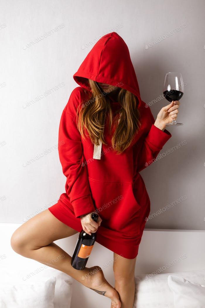 Young lady in red hoodie standing in bed and holding bottle and glass of red wine in hands
