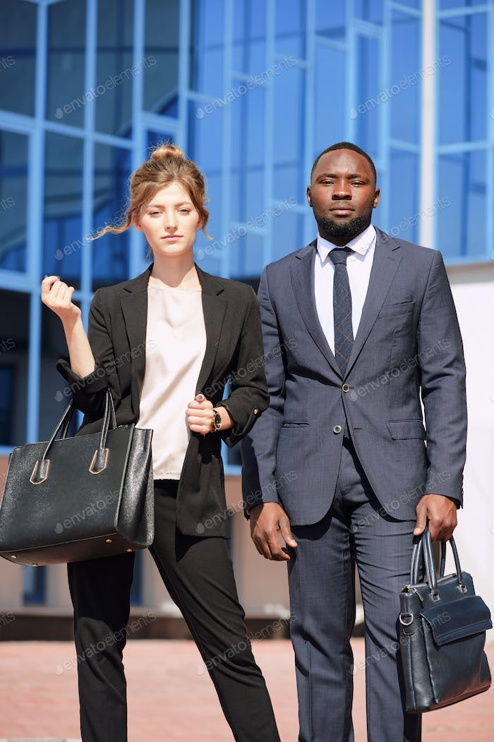 Young intercultural business professionals in formalwear standing by airport