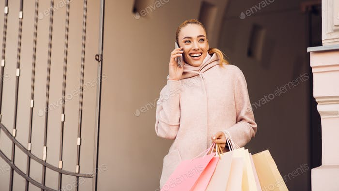 Young woman talking on phone after shopping in boutiques