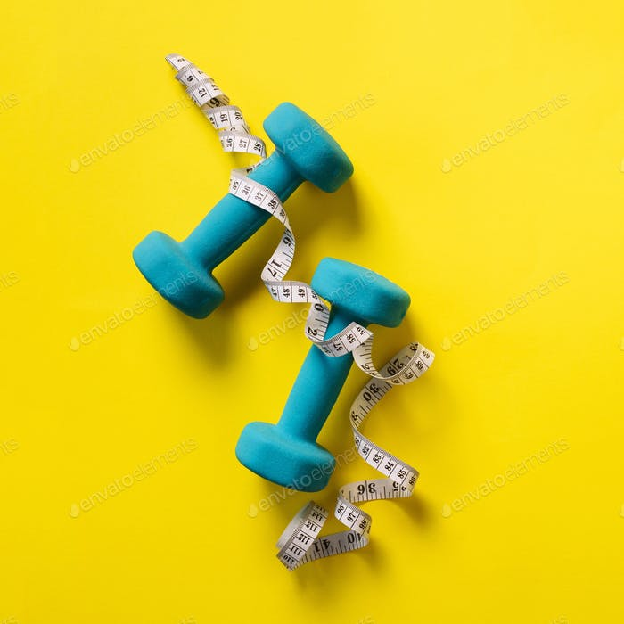 Fitness, sport concept with dumbbells and measuring tape over yellow background. Banner, copy space