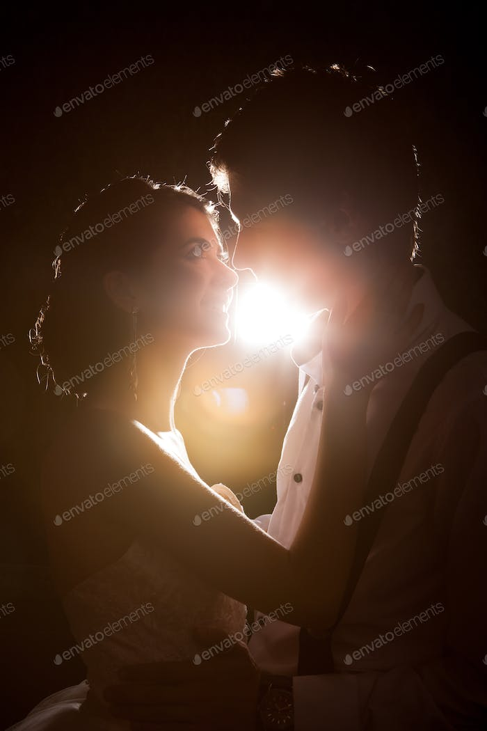 Beautiful Inlove bride and groom together backlit