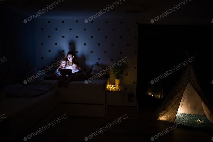 Young mother with children sitting indoors in bedroom, using laptop.