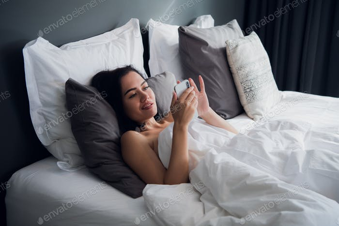 Happy attractive young European female smiling broadly while reading text message from her boyfriend