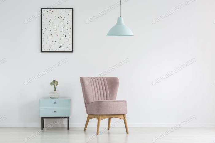 Cupboard, armchair, poster and lamp on a white, empty wall in a