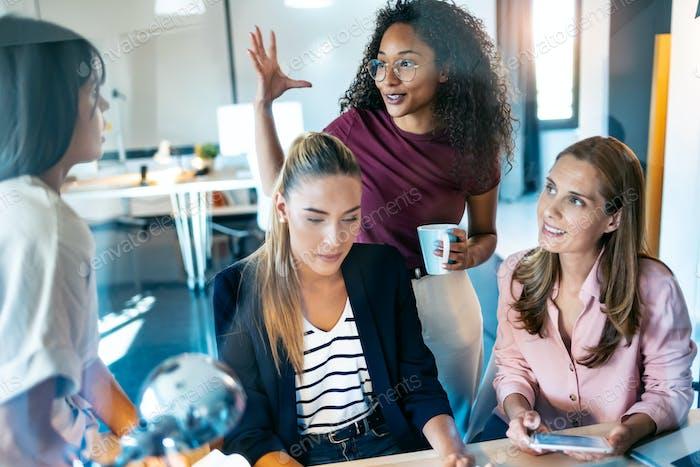 Vier Geschäftsfrauen sprechen und überprüfen die neuesten Arbeiten am Computer in einem gemeinsamen Arbeitsbereich.