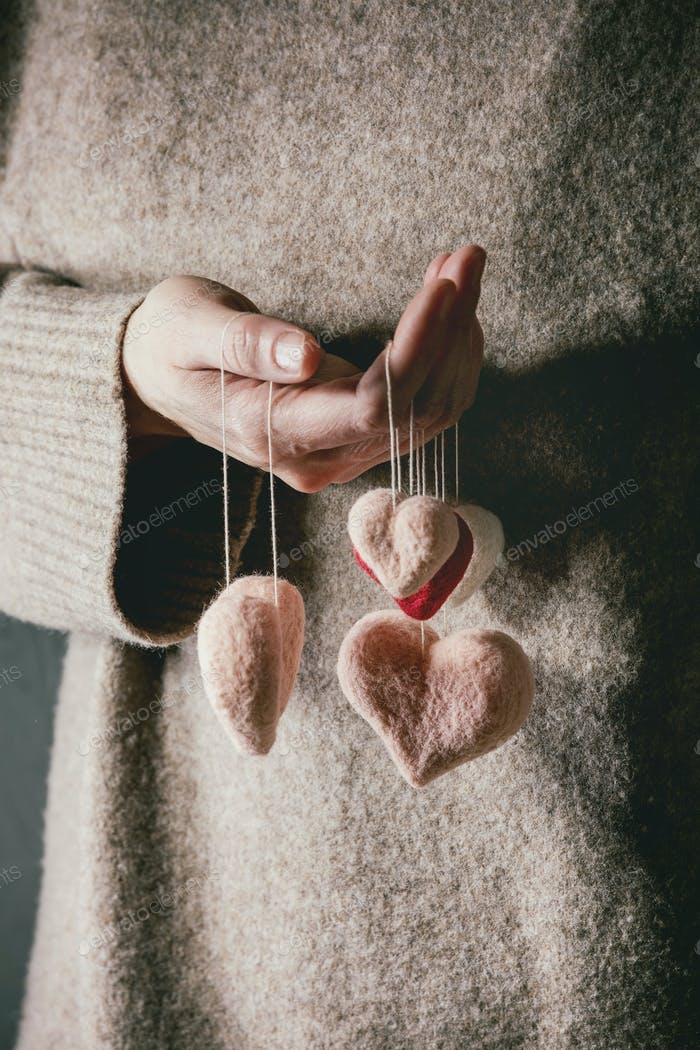 Felted hearts in female hands