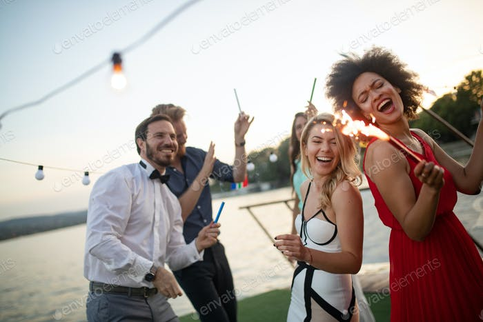 Group of friends at party dancing and smiling together