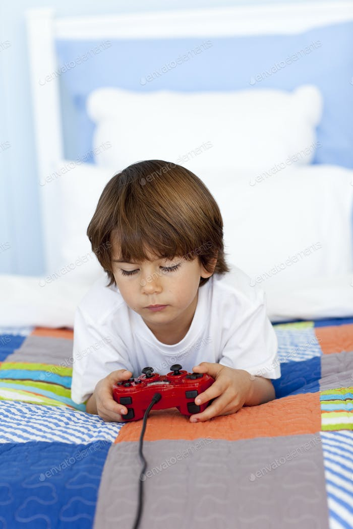 Boy playing videogames in his bedroom