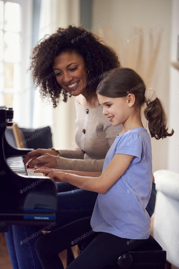 Молодая девушка учится играть на фортепиано, имея урок от учительницы