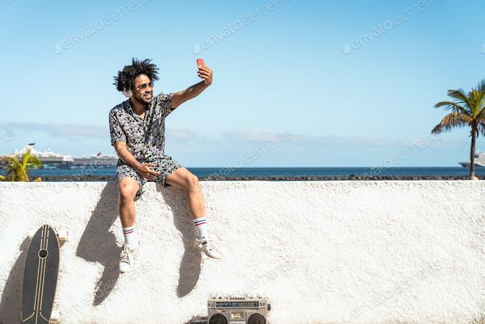 Young Latin man having fun taking selfie with mobile smartphone