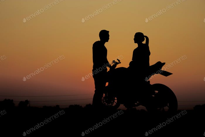 Couples with a motorcycle at sunset