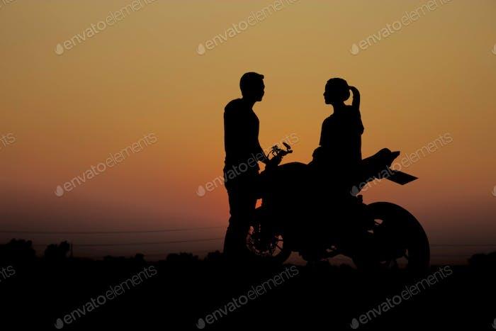 Parejas con una motocicleta al atardecer