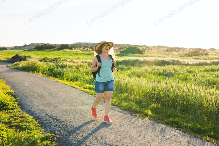 Woman traveler looking sunset at green field