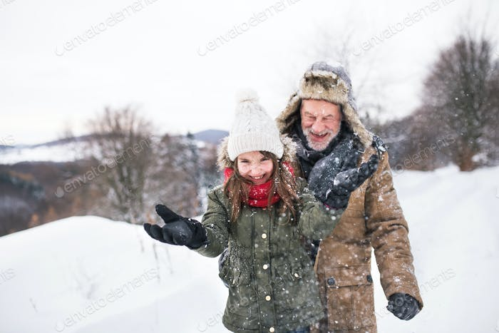 Grandfather and small girl in snow on a winter day.