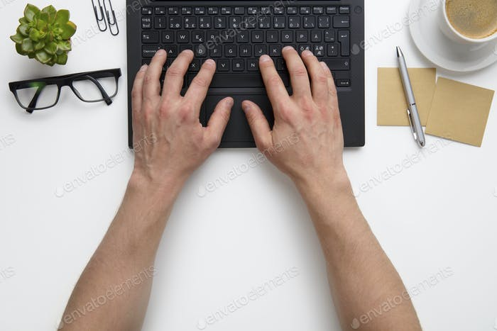 Businessman Using Laptop At White Desk In Office