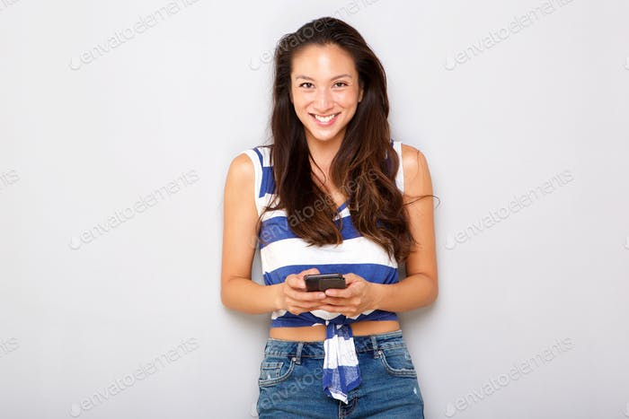 smiling young asian woman holding mobile phone