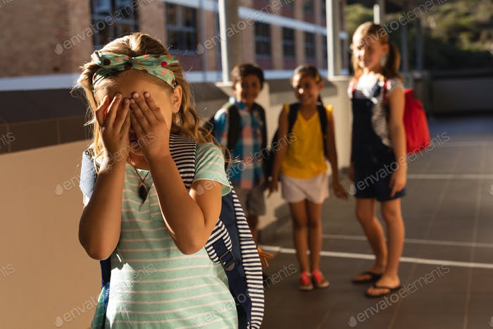 Front view of school friends bullying a crying girl in hallway of elementary school