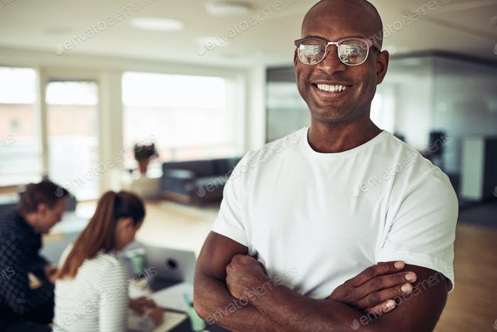 Confident African businessman smiling with colleagues working in the background