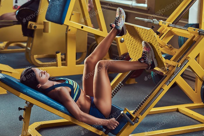 Beautiful athletic brunette in a sportswear, working out in the gym