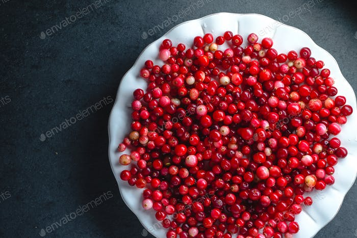 Red cranberries on a large white plate on a gray background
