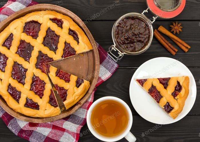 Pie with jam and tea on black wooden background.