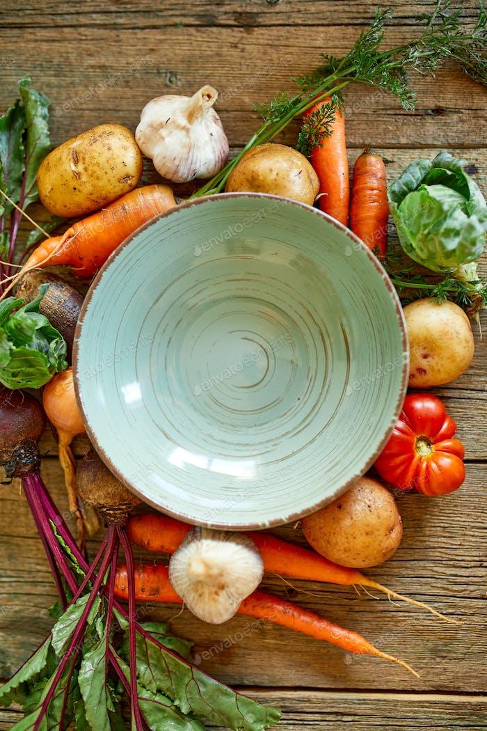 Frisches Gemüse zum Kochen von Suppe um einen runden grünen leeren Teller