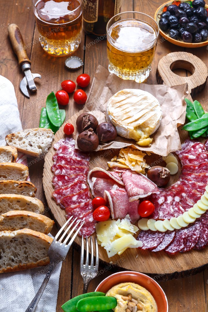 Close view of mix of delicious meat snacks on wooden board.