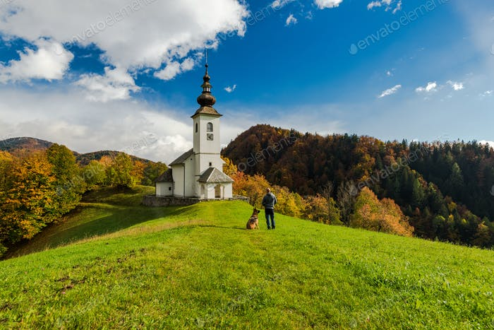 Man with dog admiring rural chapel in Slovenia