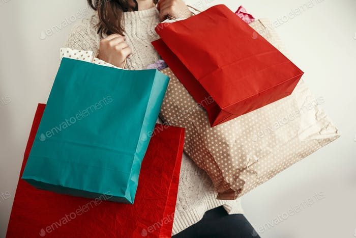 Happy Girl in sweater holding red and green paper shopping bags