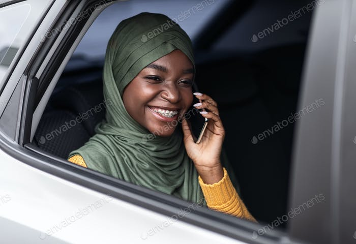 Comfortable Transport. Black Muslim Woman Having Car Ride And Talking On Cellphone