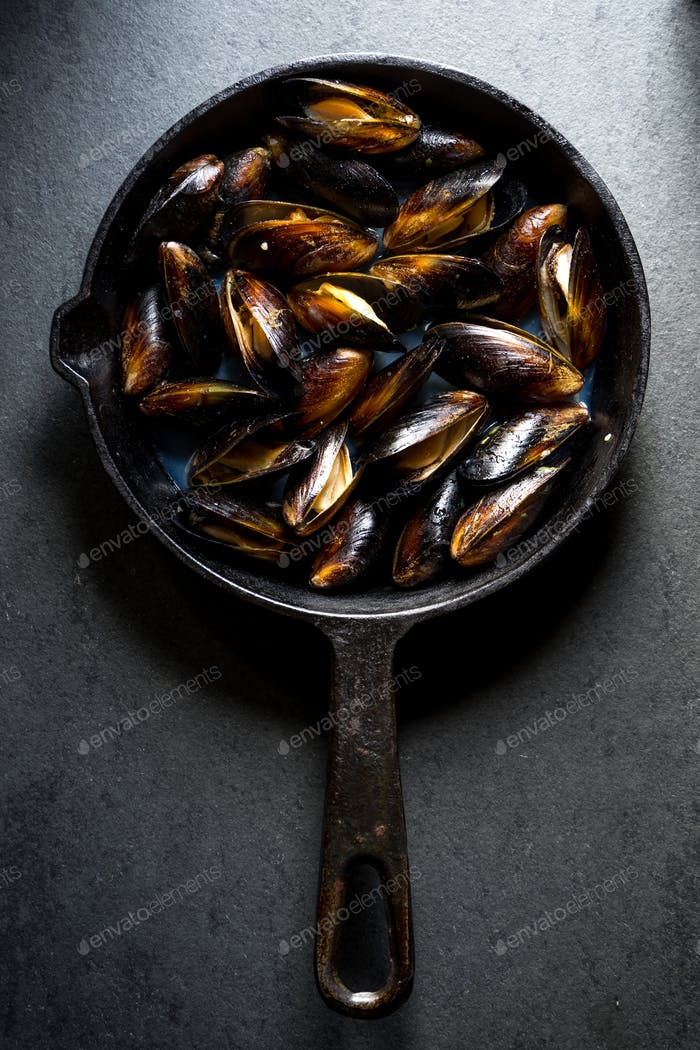 Mussels steamed on a cast-iron frying pan