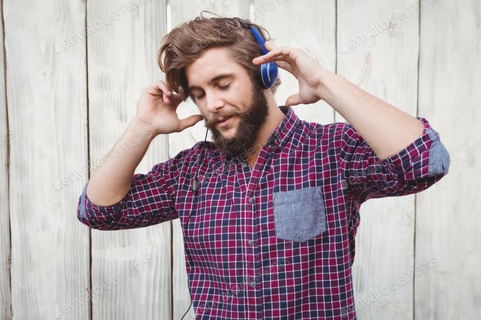 Hipster wearing headphones against wooden fence