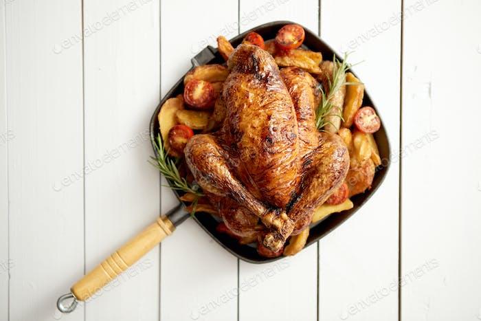 Gegrilltes ganzes Huhn in schwarzer Pfanne aus Gusseisen mit Kartoffeln, Tomaten und Rosmarin