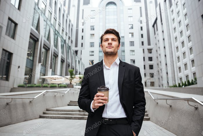 Businessman drinking take away coffee in the city