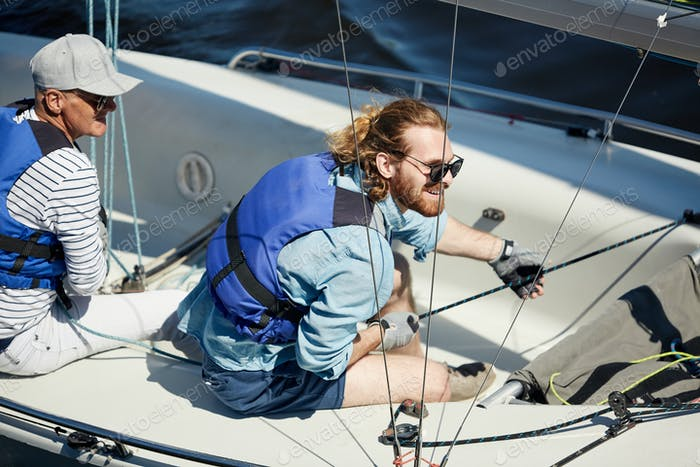 Happy man handling sailboat