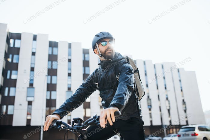 Male courier with bicycle and sunglasses delivering packages in city.