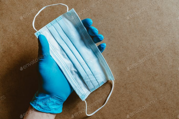 Hand in blue rubber gloves holds a medical mask.