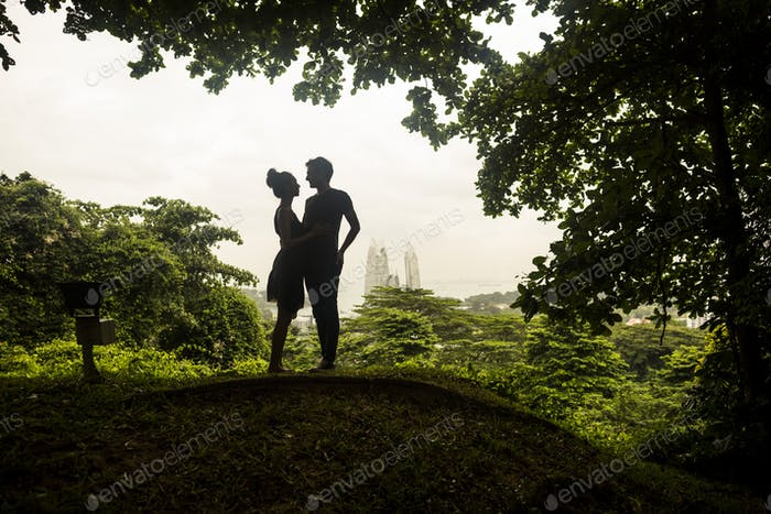Silhouette of young couple standing underneath trees in a forest, skyscrapers in the distance.