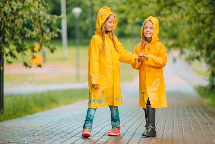 Entzückende kleine Mädchen unter dem Regen an warmen Frühlingstag