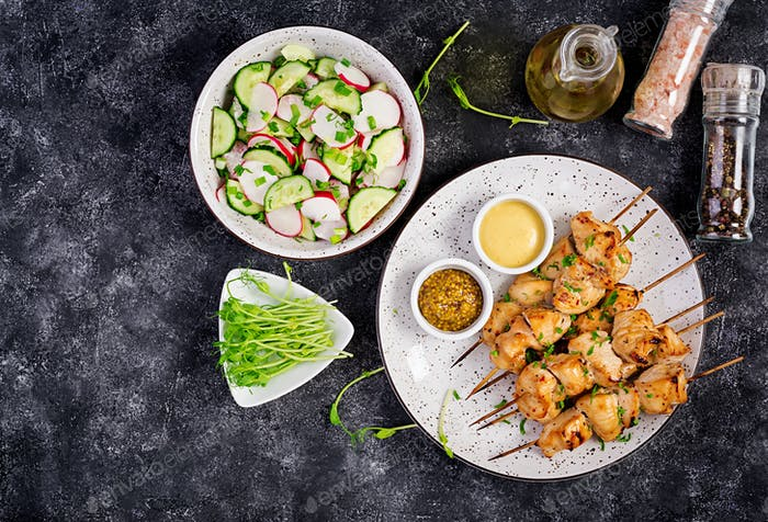 Grilled chicken kebab and salad with cucumber, radish, onion