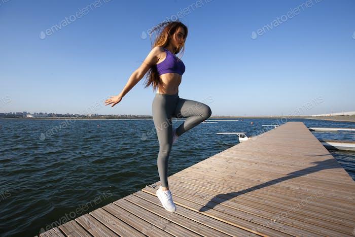 Девушка, одетая в спортивную форму, прыгает по деревянному пирсу на
